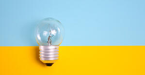 Light bulb on blue and yellow background